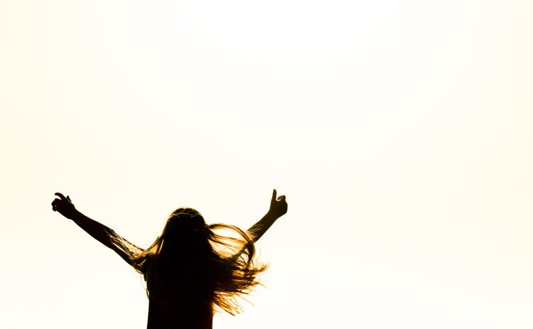 silhouette-of-woman-raising-her-hands-615334